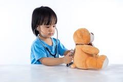 Asian Chinese little doctor girl examine teddy bear Stock Photo