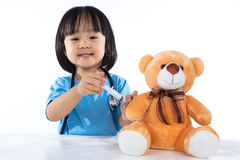 Asian Chinese little doctor girl giving injection to teddy bear Stock Photos
