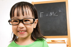 Asian Chinese little girl againts blackboard with formulas Stock Photos