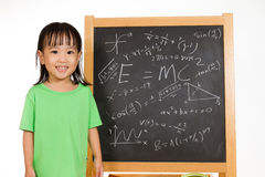 Asian Chinese little girl againts blackboard with formulas Stock Photo