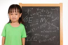 Asian Chinese little girl againts blackboard with formulas Stock Photography