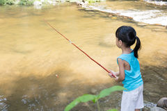 Asian Chinese little girl angling with fishing rod. At the river shore Royalty Free Stock Images