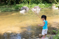 Asian Chinese little girl angling with fishing rod. At the river shore Royalty Free Stock Photography