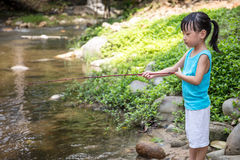 Asian Chinese little girl angling with fishing rod. At the river shore Stock Images