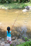 Asian Chinese little girl angling with fishing rod. At the river shore Stock Photos