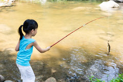 Asian Chinese little girl angling with fishing rod. At the river shore Royalty Free Stock Image
