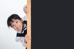 Asian Chinese little girl behind the blackboard. In white background royalty free stock photos