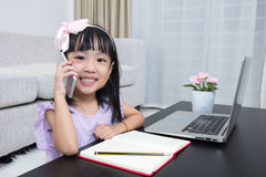 Asian Chinese little girl busy reading mobile phone and laptop Royalty Free Stock Photos