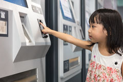Asian Chinese little girl buying admission ticket at MRT station Royalty Free Stock Photo