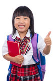 Asian Chinese little girl carrying school bag with thumbs up Royalty Free Stock Images