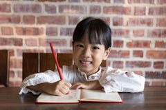 Asian Chinese little girl doing homework. At indoor cafe Stock Images