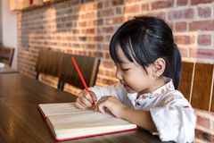 Asian Chinese little girl doing homework. At indoor cafe Stock Photography