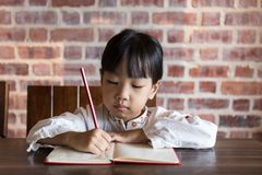 Asian Chinese little girl doing homework. At indoor cafe Stock Photo