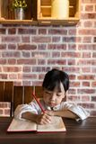 Asian Chinese little girl doing homework. At indoor cafe Royalty Free Stock Image