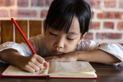 Asian Chinese little girl doing homework. At indoor cafe Royalty Free Stock Images