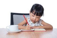 Asian Chinese little girl doing homework. In isolated white background Stock Images
