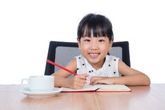 Asian Chinese little girl doing homework. In isolated white background Royalty Free Stock Images