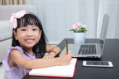 Asian Chinese little girl doing homework with laptop. In the living room at home royalty free stock photography