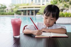 Asian Chinese little girl doing homework. At outdoor cafe Royalty Free Stock Photo