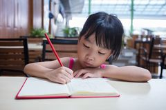 Asian Chinese little girl doing homework. At outdoor cafe Stock Photos