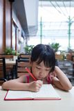 Asian Chinese little girl doing homework. At outdoor cafe Stock Images