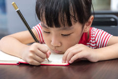 Asian Chinese little girl doing homework. At outdoor cafe Royalty Free Stock Image