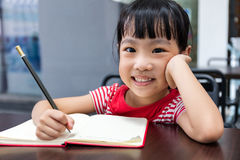 Asian Chinese little girl doing homework. At outdoor cafe Stock Image
