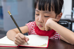Asian Chinese little girl doing homework. At outdoor cafe Royalty Free Stock Images