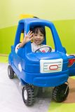 Asian Chinese little girl driving toy car. At indoor playground Royalty Free Stock Image