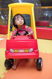 Asian Chinese little girl driving toy car at playground. Asian Chinese little girl driving toy car at indoor playground Royalty Free Stock Photo