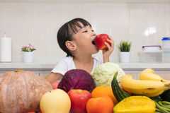 Asian Chinese little girl eating apple infront fruit and vegetab Stock Image