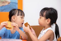 Asian Chinese little girl eating burger and fried chicken. At indoor restaurant royalty free stock image