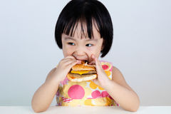 Asian Chinese little girl Eating Burger Stock Photography
