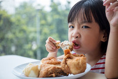 Asian Chinese little girl eating fried chicken Royalty Free Stock Photos