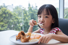 Asian Chinese little girl eating fried chicken Royalty Free Stock Photo