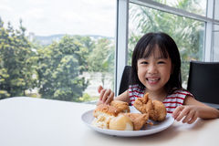 Asian Chinese little girl eating fried chicken Stock Photo