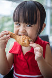 Asian Chinese little girl eating fried chicken Stock Image