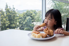 Asian Chinese little girl eating fried chicken. At indoor restaurant stock images