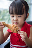Asian Chinese little girl eating fried chicken Royalty Free Stock Photography