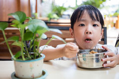 Asian Chinese little girl eating fried rice Stock Images