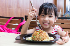 Asian Chinese little girl eating fried rice stock photo