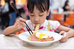 Asian Chinese little girl eating noodles with chopsticks stock photo