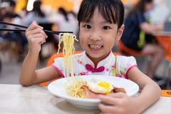 Asian Chinese little girl eating noodles with chopsticks royalty free stock images