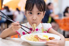 Asian Chinese little girl eating noodles with chopsticks royalty free stock image