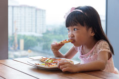 Asian Chinese little girl eating pizza pepperoni. In the restaurant stock photography