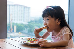Asian Chinese little girl eating pizza pepperoni Royalty Free Stock Photo