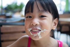 Asian Chinese little girl eating spaghetti. At outdoor cafe Stock Photos