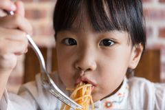Asian Chinese little girl eating spaghetti bolognese. In the restaurant Royalty Free Stock Photo