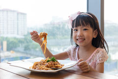 Asian Chinese little girl eating spaghetti bolognese Stock Photos