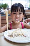 Asian Chinese little girl eating spaghetti. At outdoor cafe Royalty Free Stock Photo